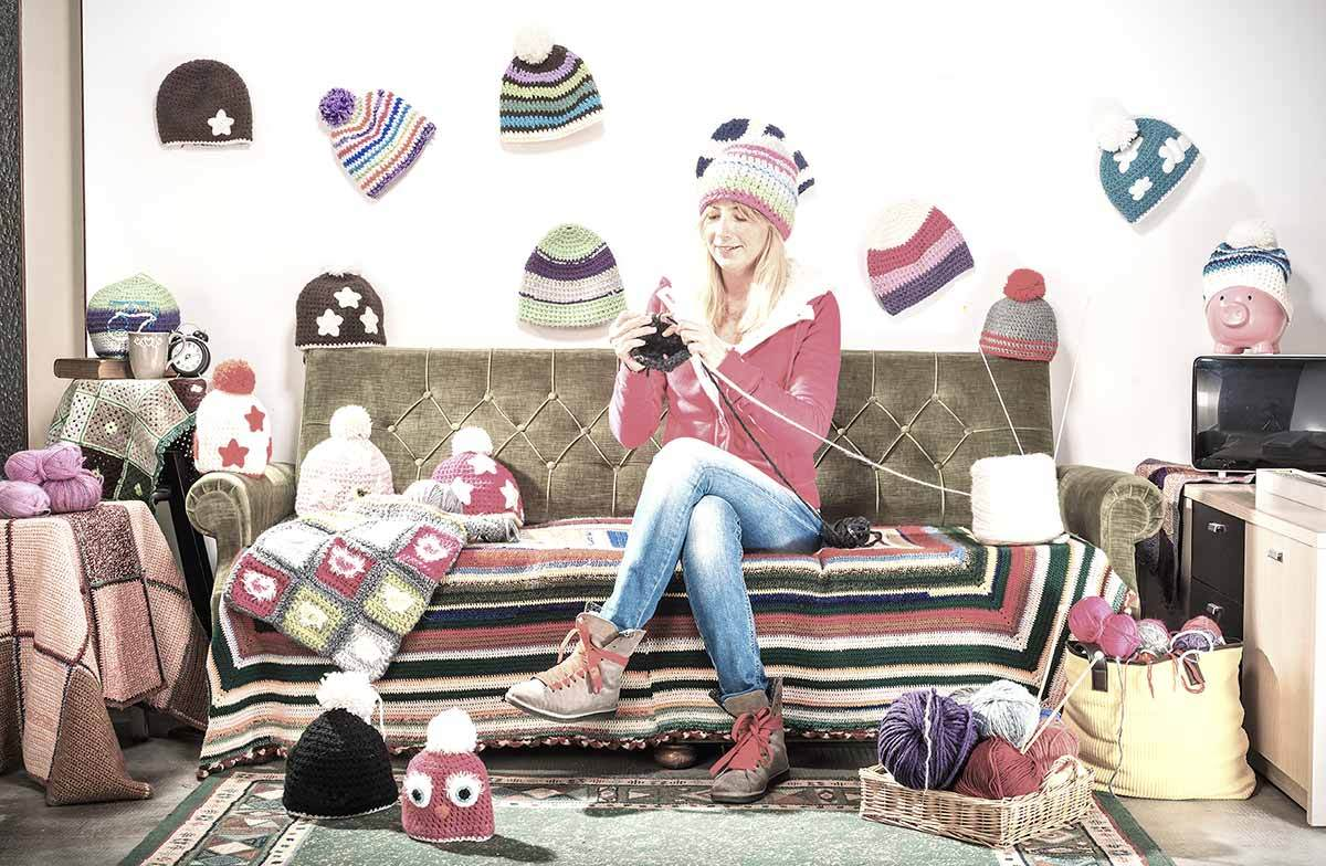 Young woman crocheting hats on a couch, surrounded by crocheted hats.