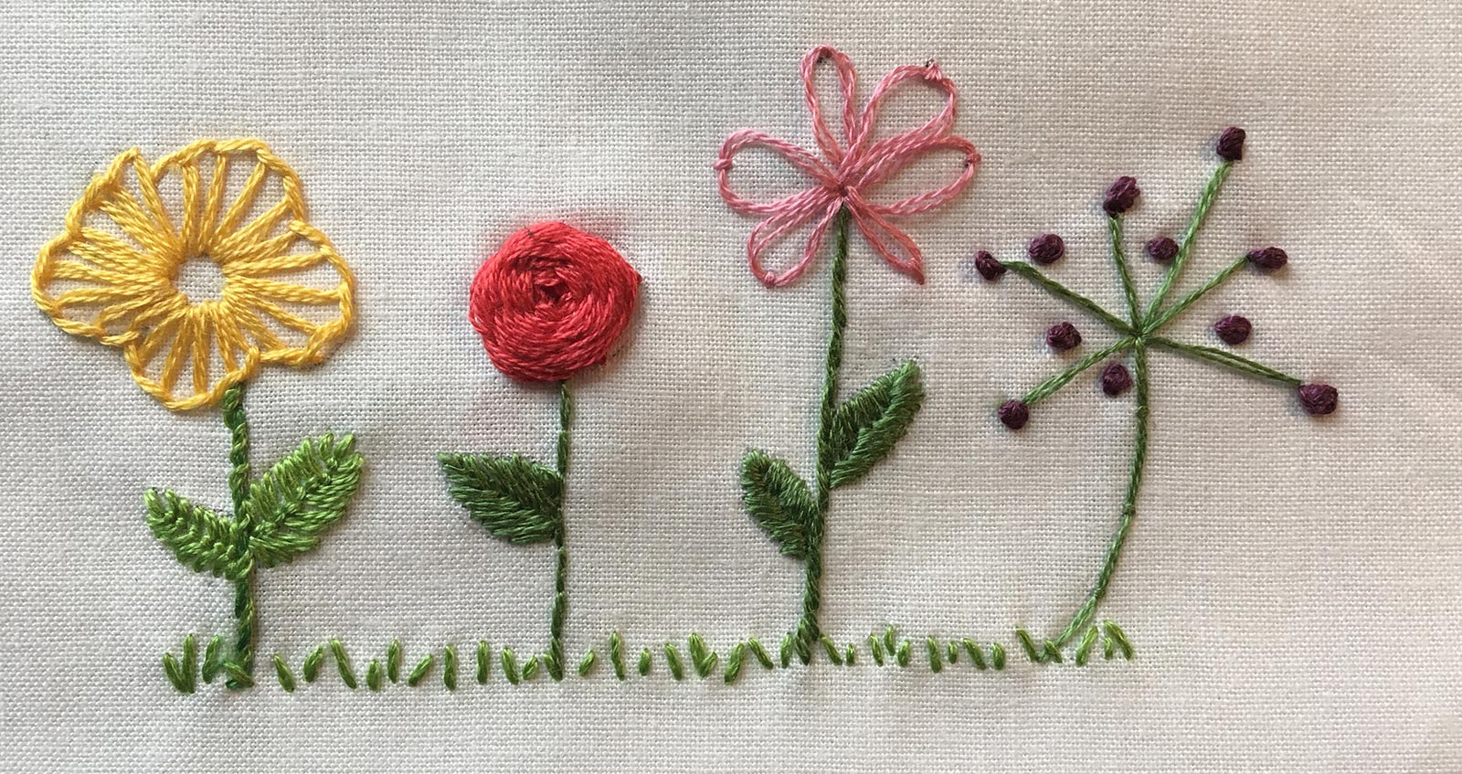 Multiple, colored flowers stitched with different embroidery stitches.