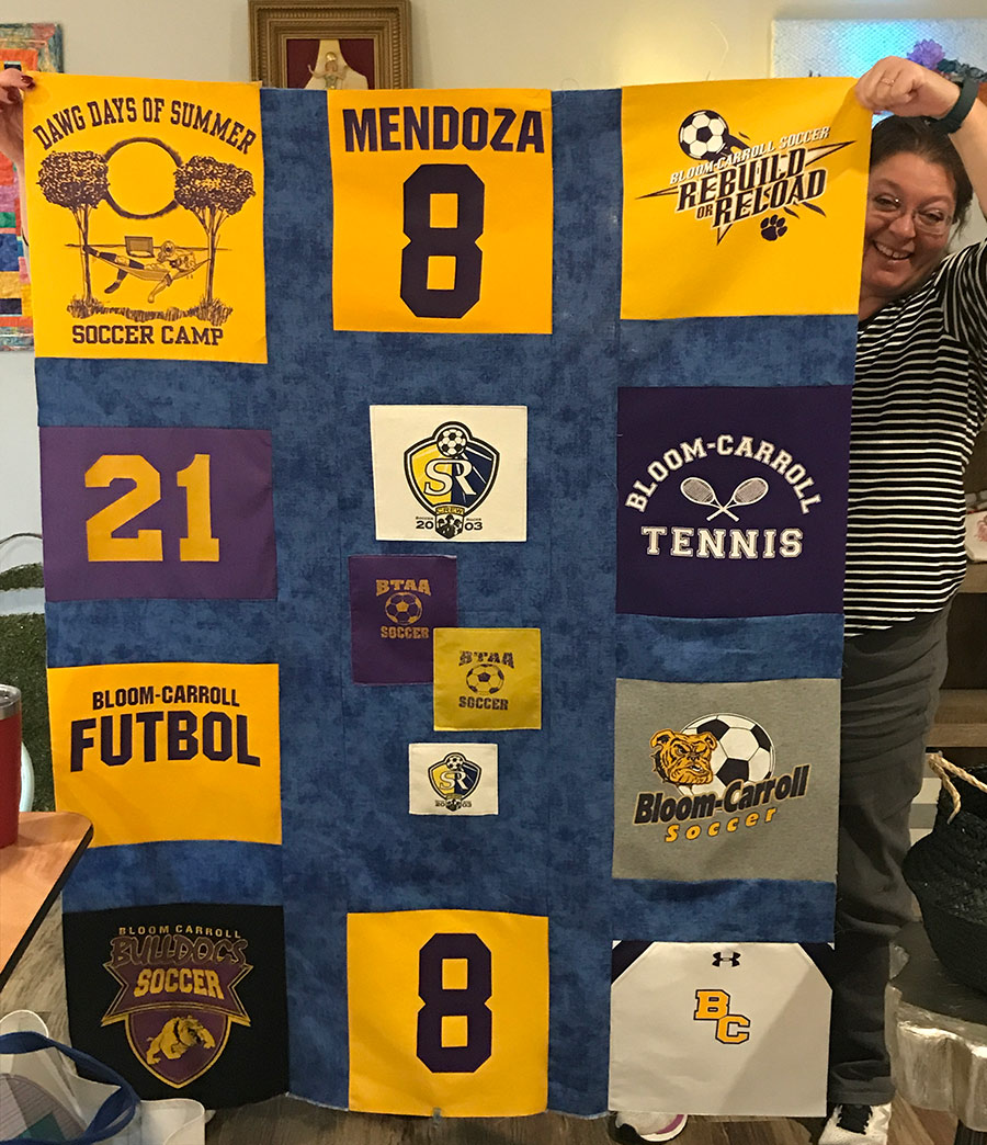 Woman holding completed T-Shirt Quilt top featuring multiple T-shirts.