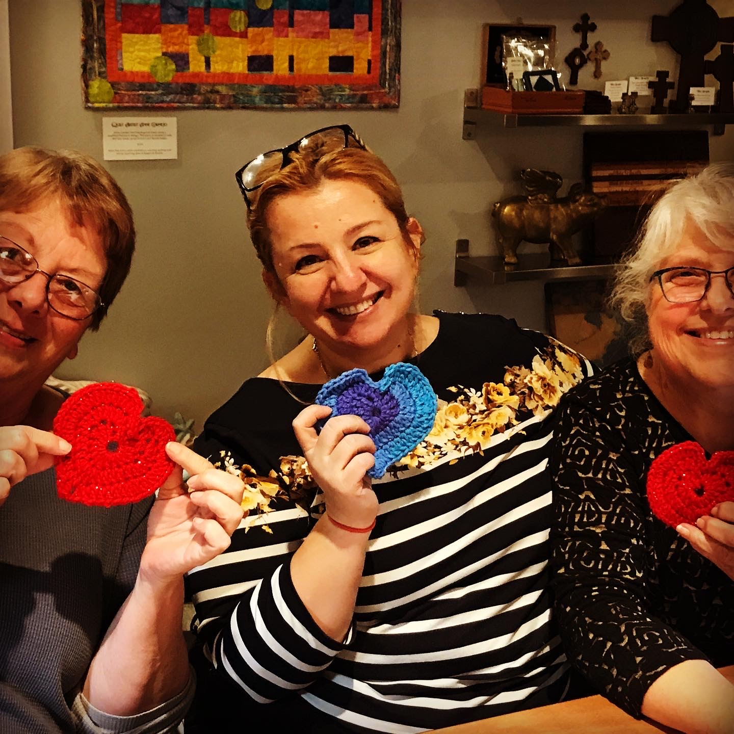 Three women posing with their crocheted heart projects.