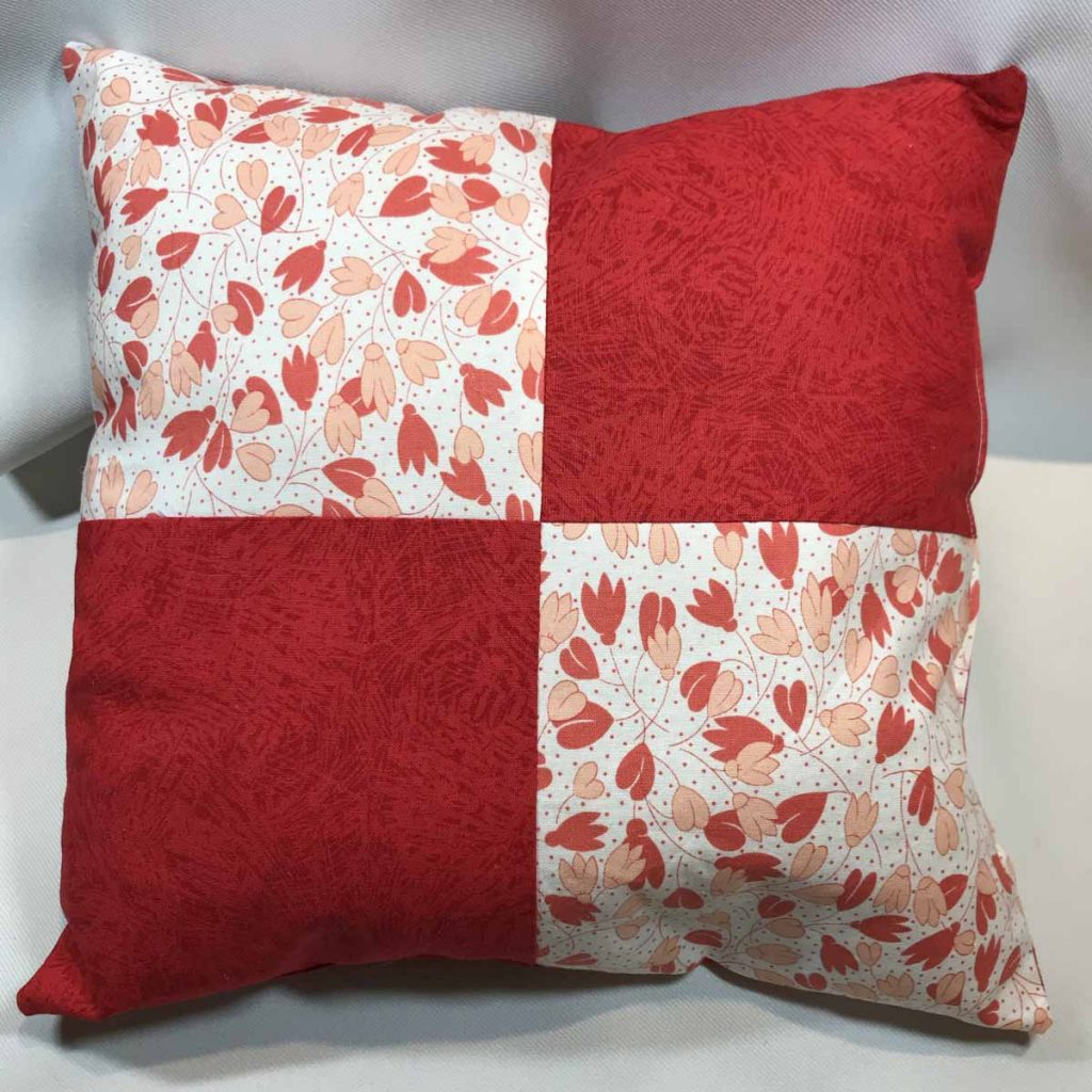Bright orange-red pillow with contrasting squares in white with orange-red pattern.