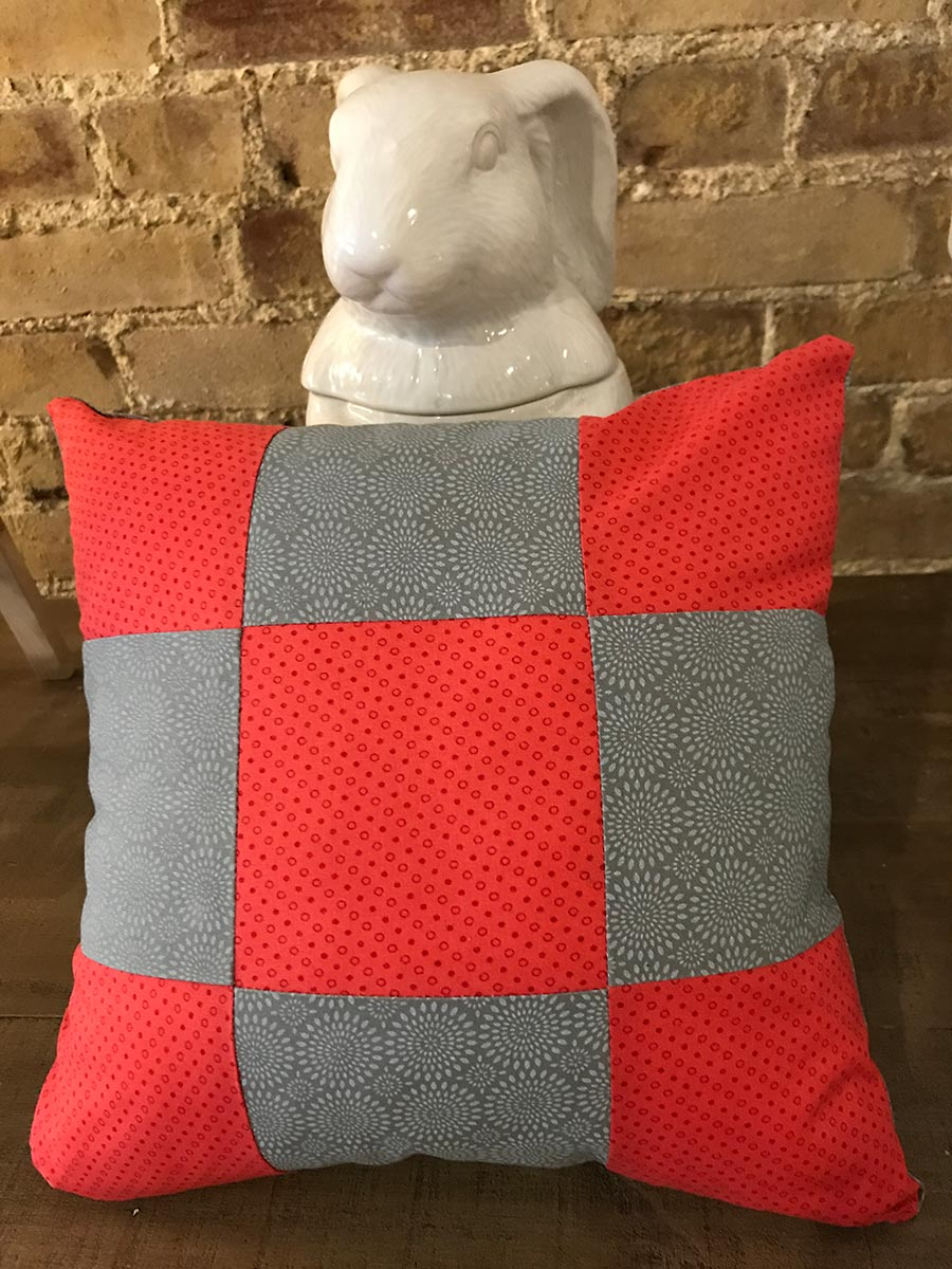 Red and gray checked pattern stuffed pillow in front of white ceramic rabbit.