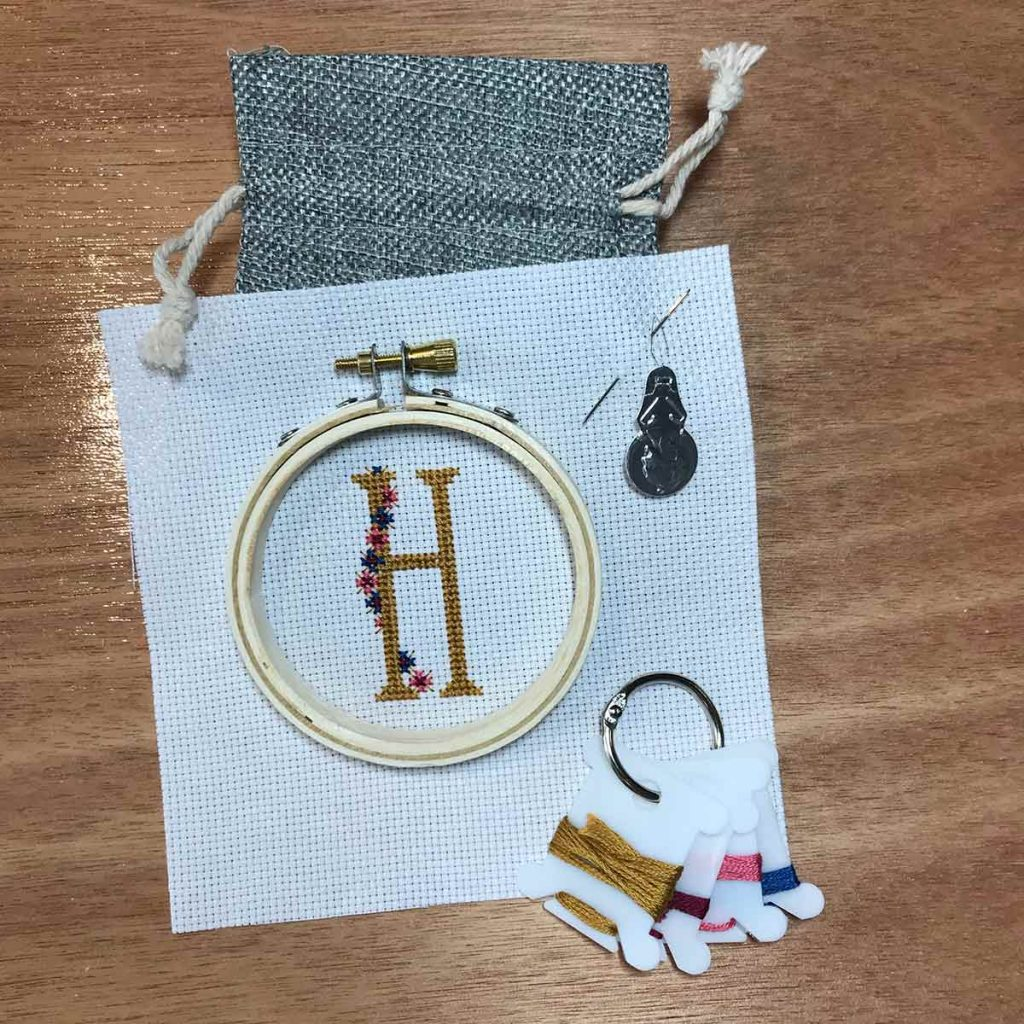 Embroidery hoop with cross stitch letter H, thread, needle and needle threader