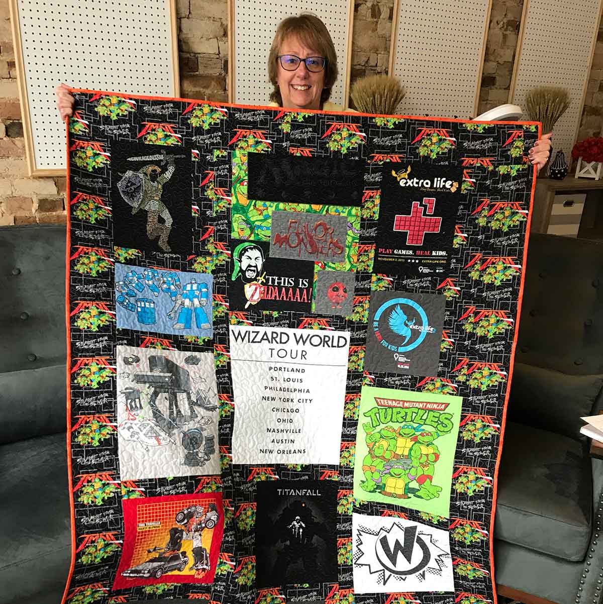 Denise Wright holds a T-shirt quilt featuring gamer motif.