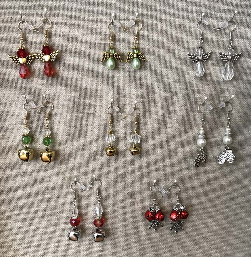 Eight pairs of holiday-themed dangle earrings featuring angels, mittens and jingle bells.
