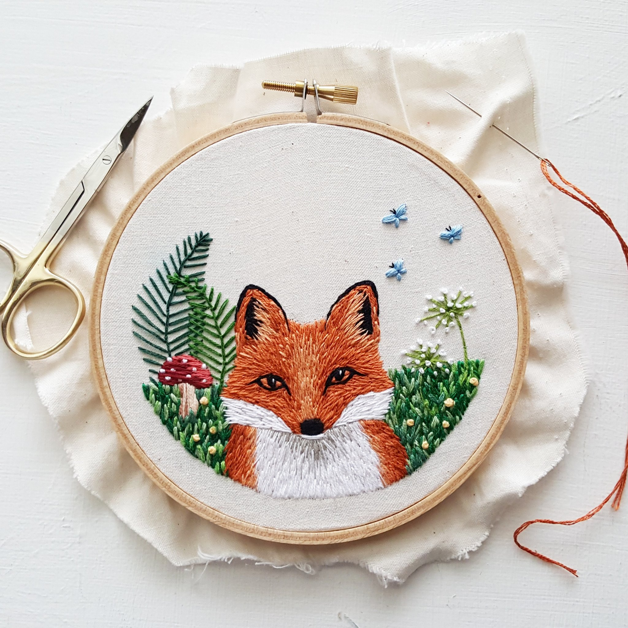 Embroidered fox with green background in embroidery hoop