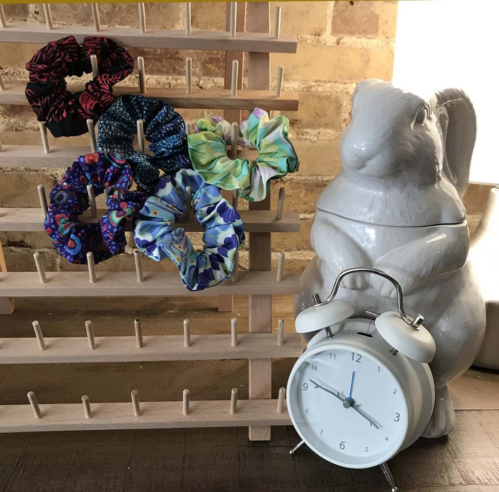 Ceramic white rabbit with clock next to bobbin stand with five colorful scrunchies.