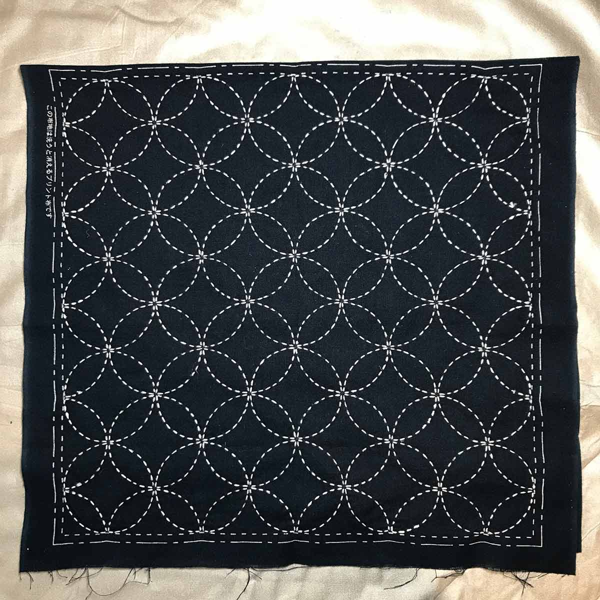 Dark blue fabric with white thread sacred geometry pattern done in Sashiko style.