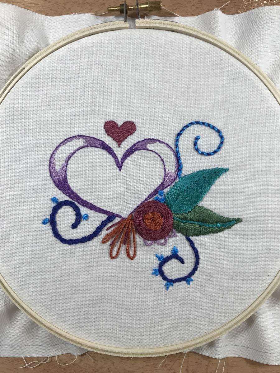 Decorative heart design with flower and embellishments stitched using multiple embroidery stitches.