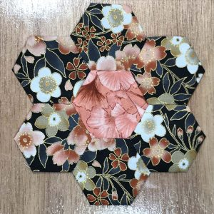 Fabric pieces sewn in the English Paper Piecing method in the shape of a flower.