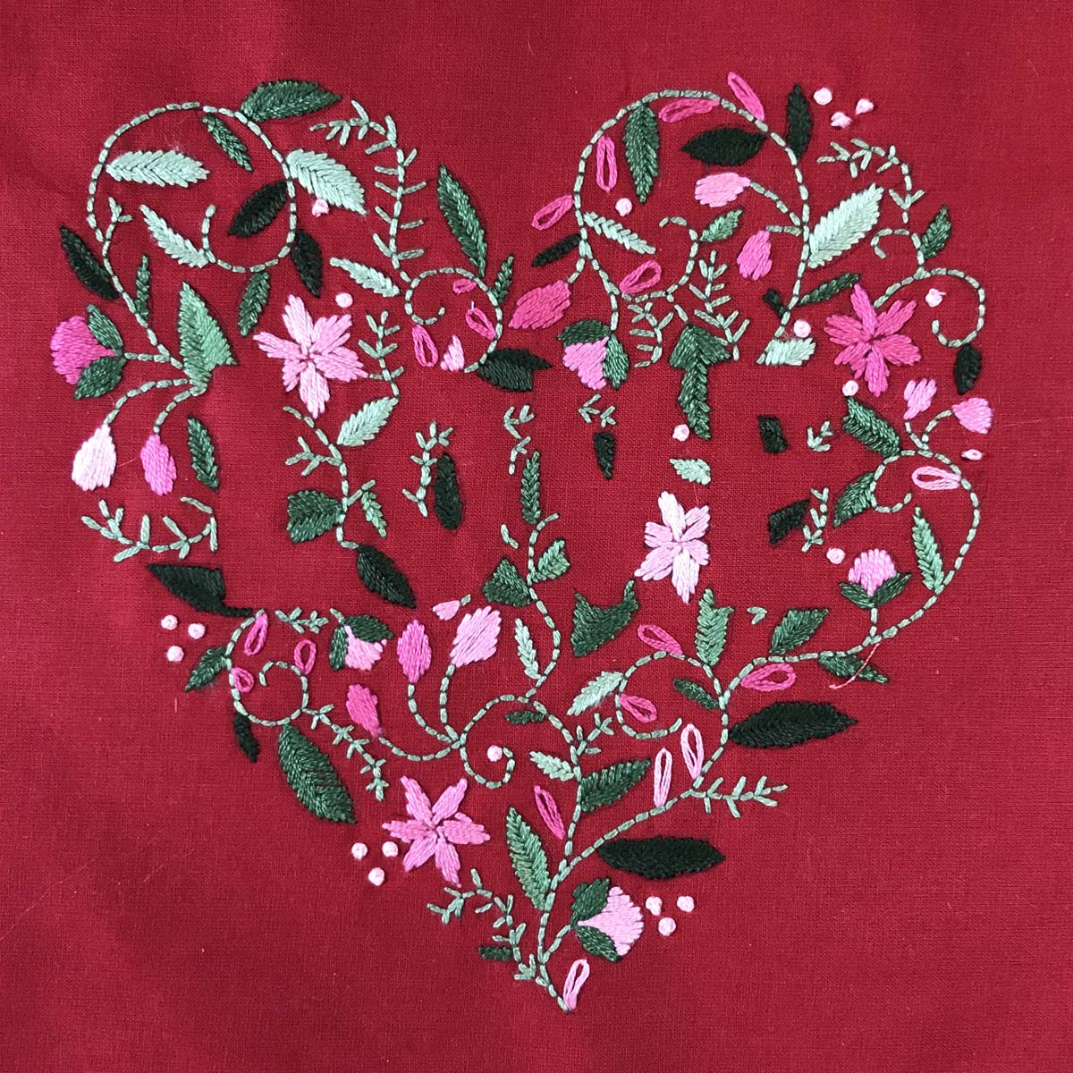 Hand embroidered heart shape with the word LOVE in the center