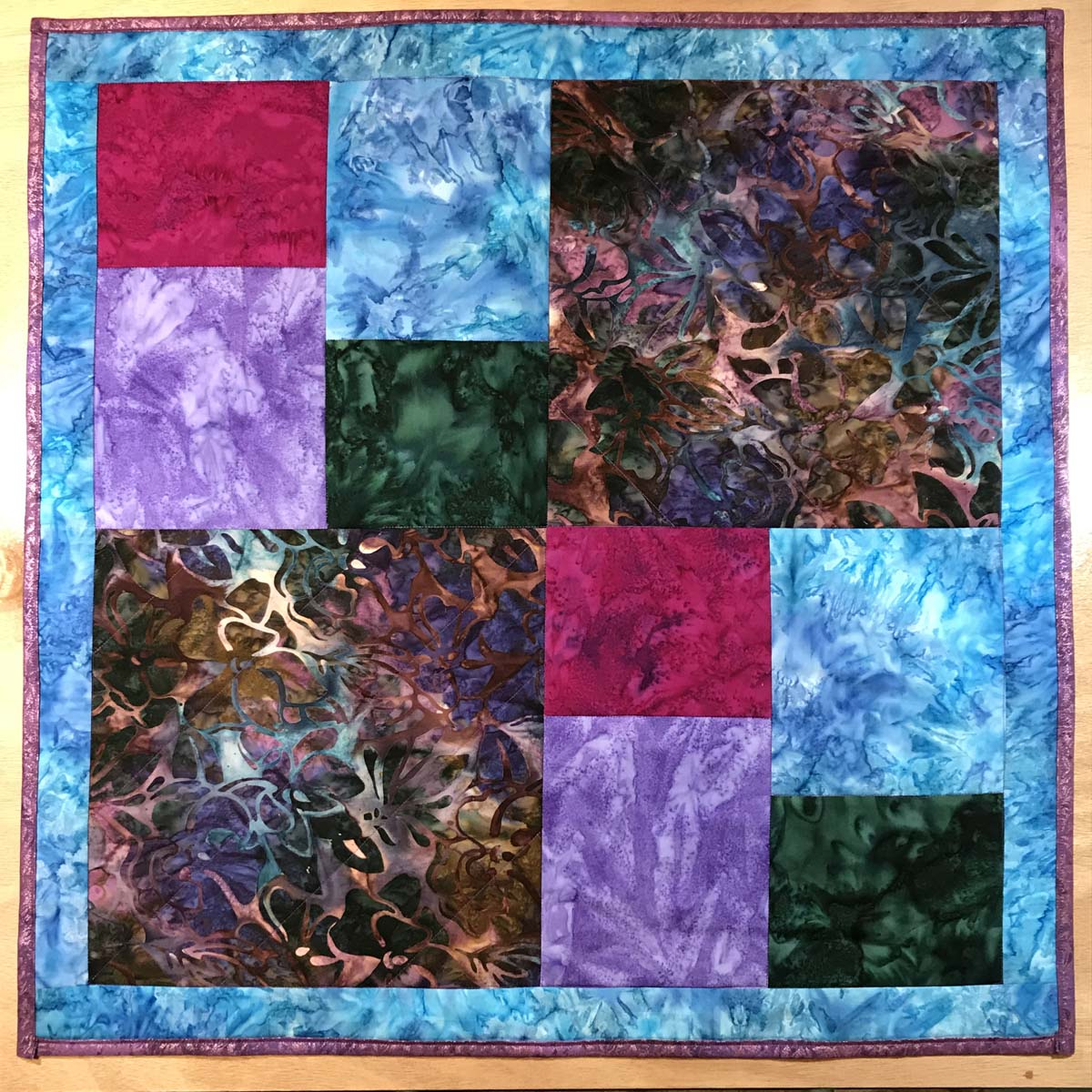 Multiple block, colorful quilt in batik fabrics of blue, purple, scarlet and earth tones.