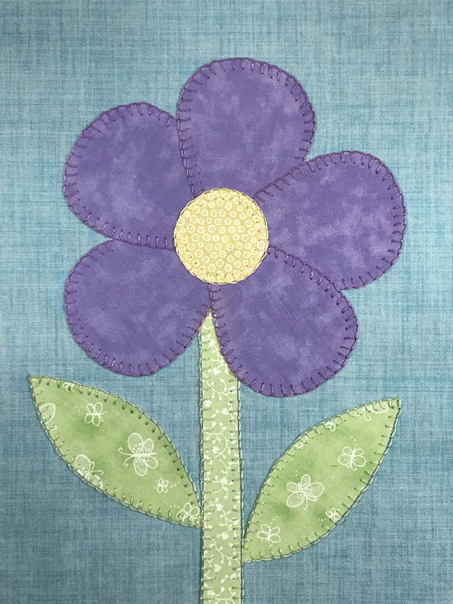 Purple fabric flower with green stem and leaves cut out and appliquéd to fabric.