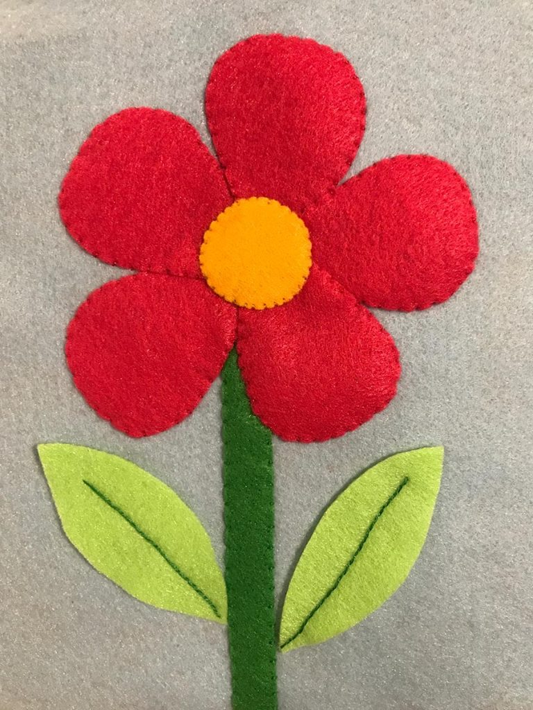 Red felt flower with green stem and leaves sewn to felt background.
