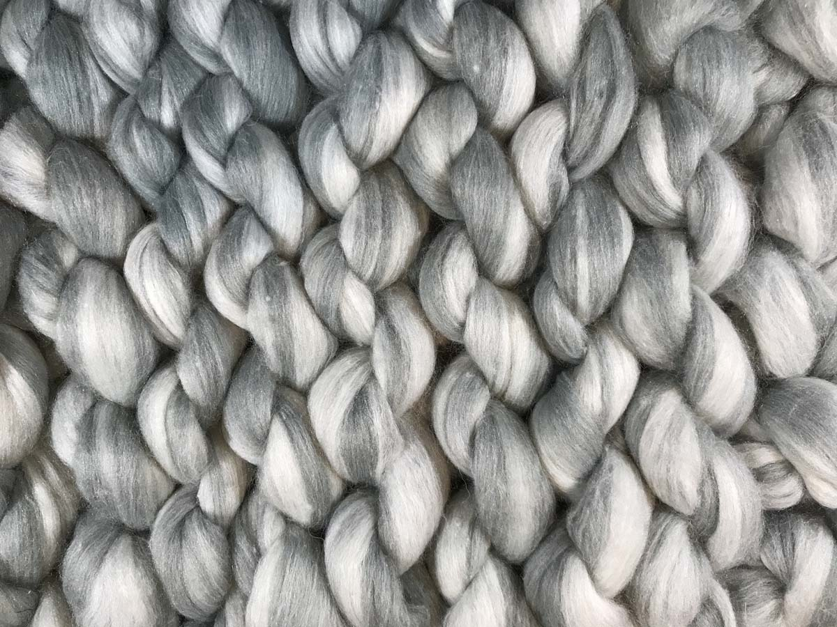 Gray and white giant yarn knitted into a throw, showing back view of stitches.