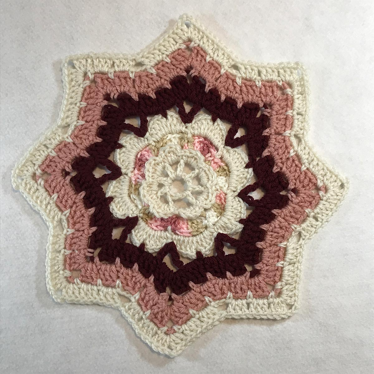 Eight-point star pattern crochet with ivory, dusty rose, maroon and pink layers.