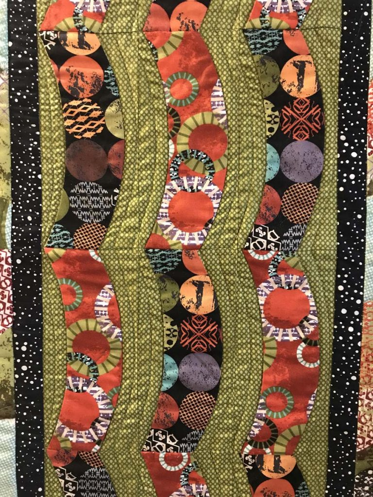 Quilted table runner with curved pattern.