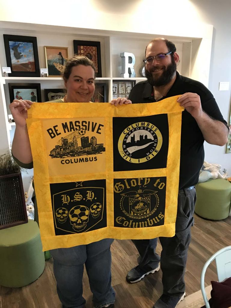 Couple holding completed T-Shirt Quilt top.