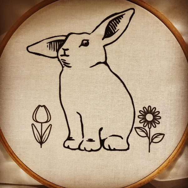 Illustration of a bunny on fabric inside an embroidery hoop