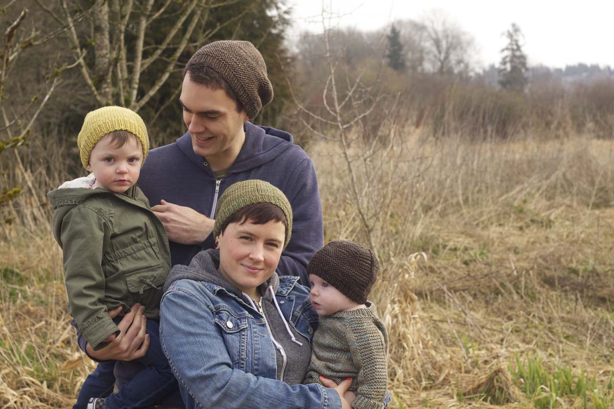 Young family outdoors all wearing knitted hats.