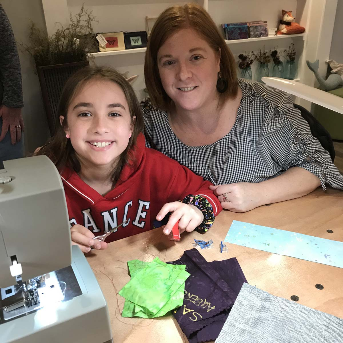 Child seated at sewing machine with adult next to her.