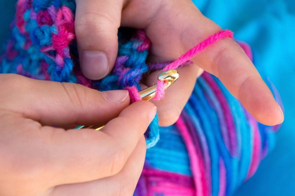 Child's hands crocheting with pink and blue yarn.