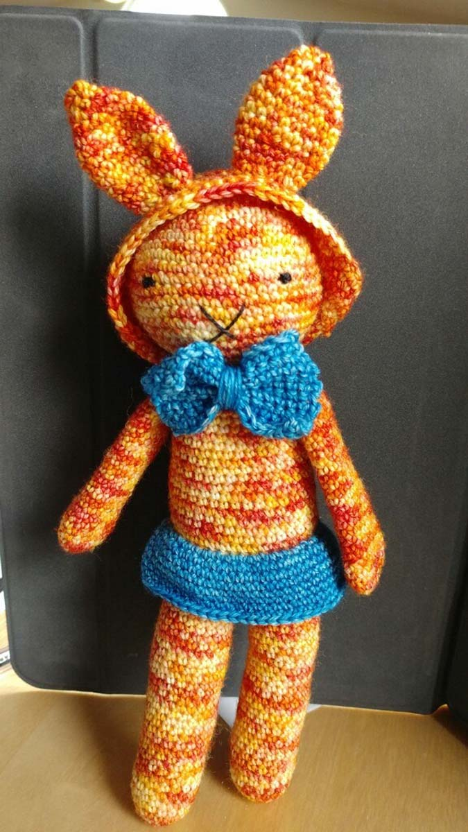 Orange patterned Amigurumi crochet rabbit with turquoise skirt and bow tie.