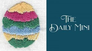 Daily Mini announcement with embroidered Easter egg with wavy multi-colored stripes in satin stitch.