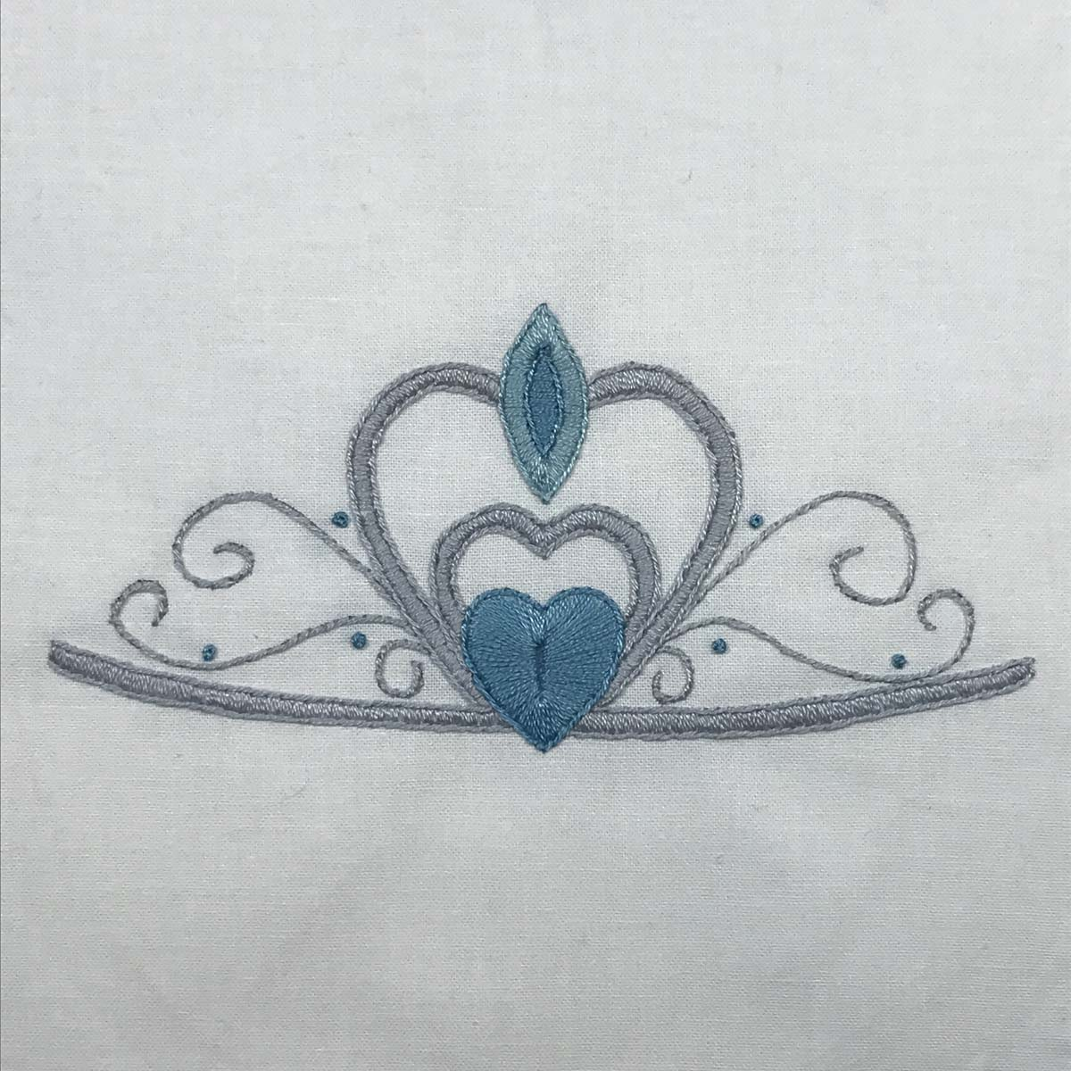 Hand-embroidered princess crown with light blue stitched gems.