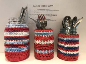 Set of three Mason jars fitted with red, white and blue crochet cozy covers.