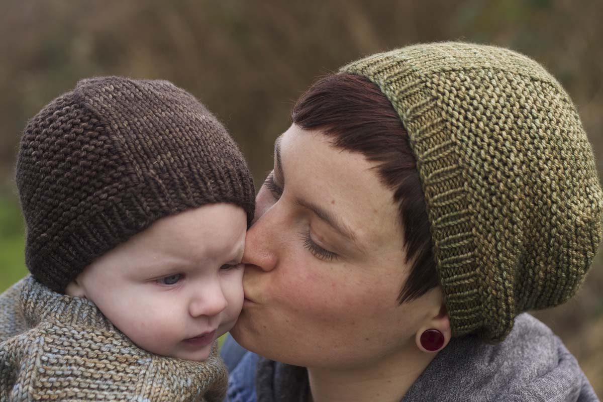 Mother kissing child - both wearing the knitted Barley Hat.