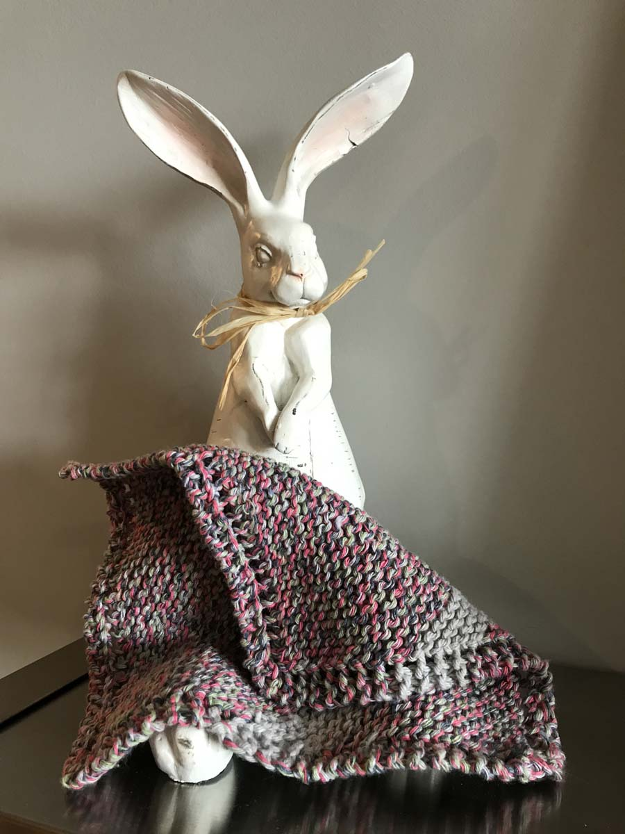 Rabbit statue with knitted cotton washcloth draped over its feet.