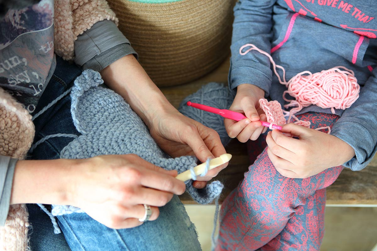 Mother and daughter crochet together.
