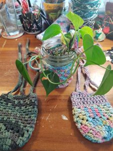 Three crocheted Mason Jar Cozies in a variety of colors and styles.
