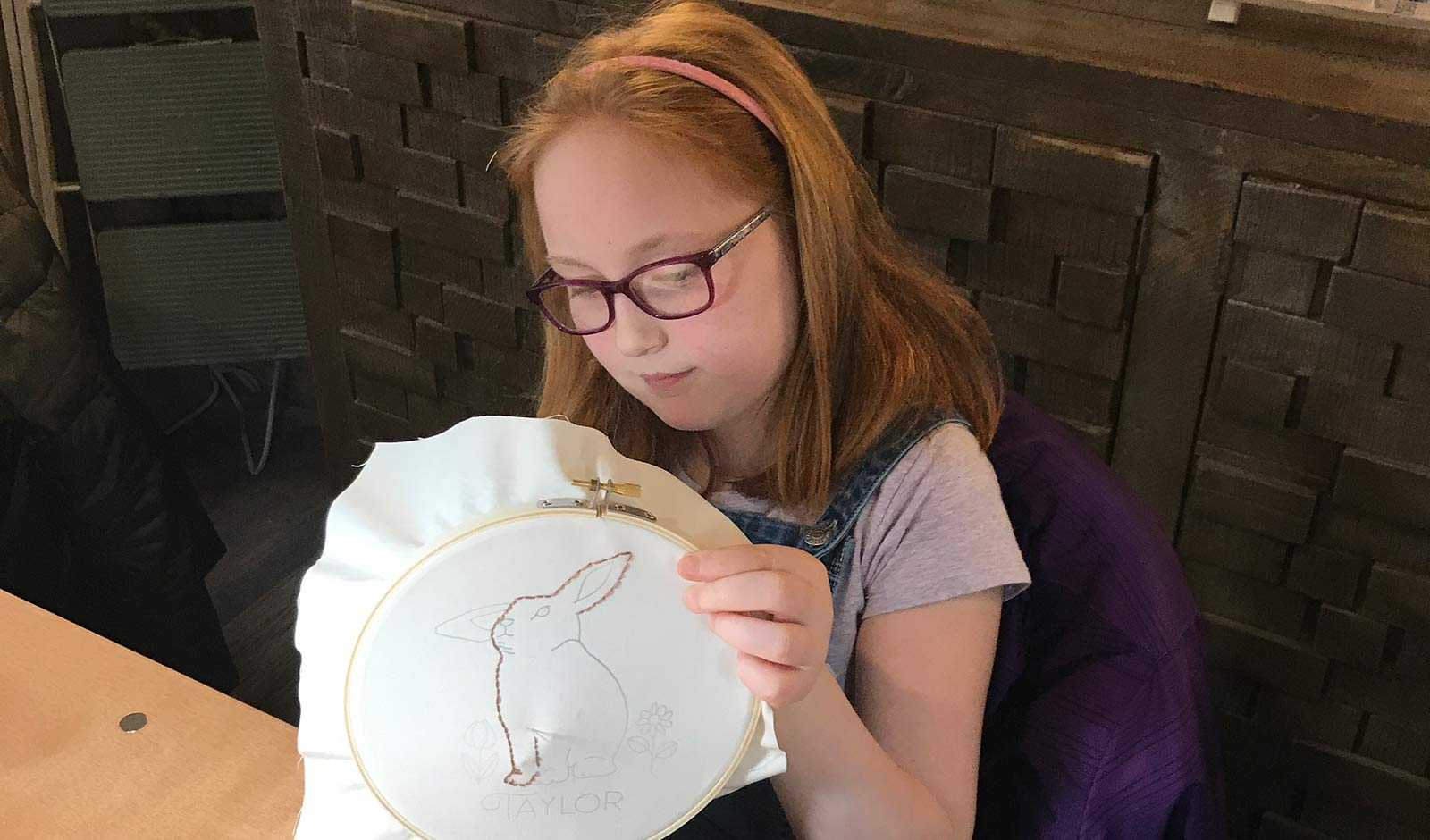 Young girl stitching rabbit pattern in a hoop.