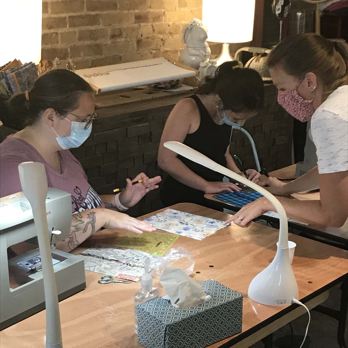 Mother and daughter sewing masks with instructor