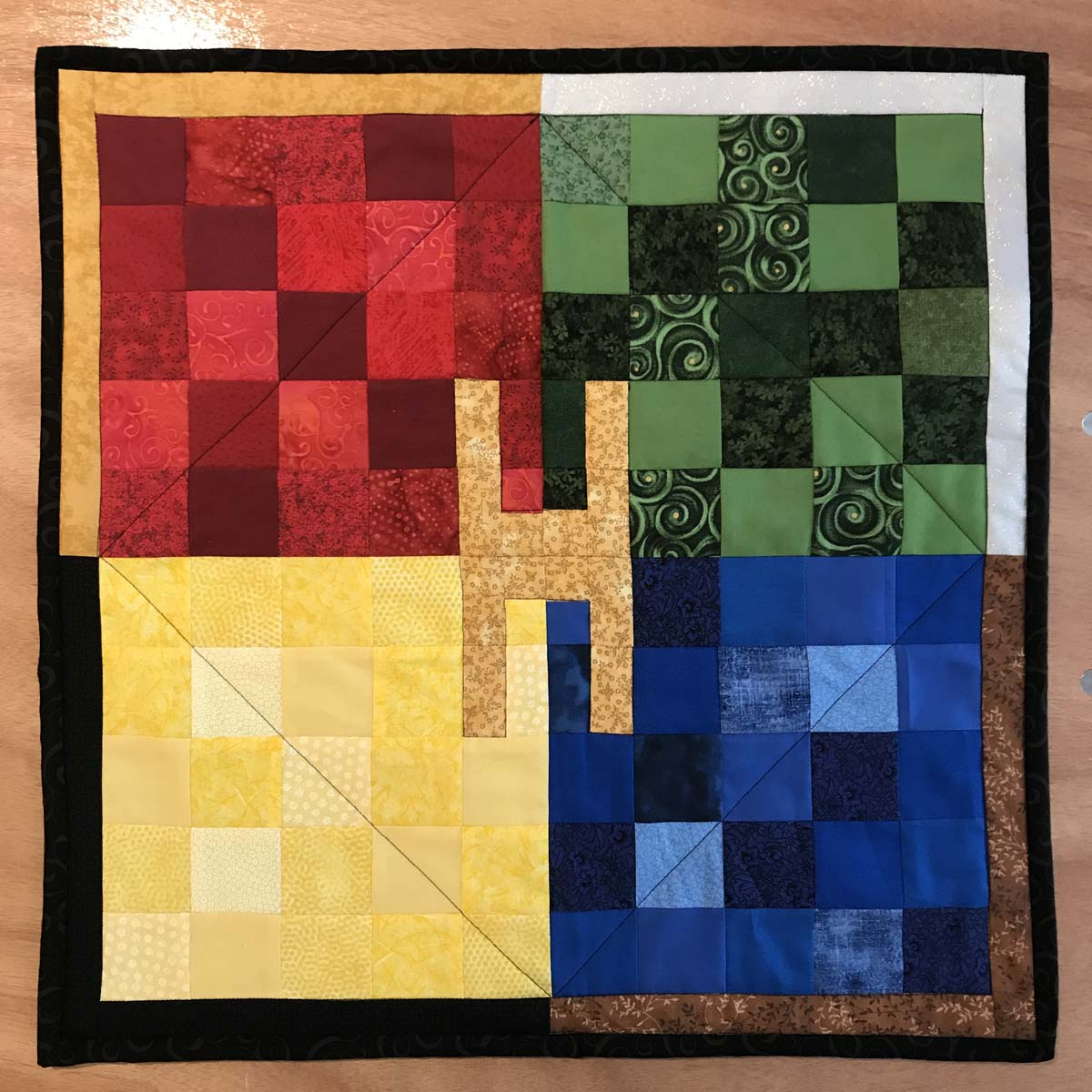 Decorative quilted wall hanging in primary colors using small blocks.