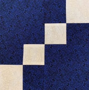 Blue and white pattern quilt block on diagonal.