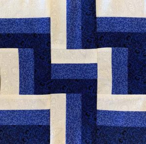 Blue, dark blue and white L-shaped pattern quilt block.