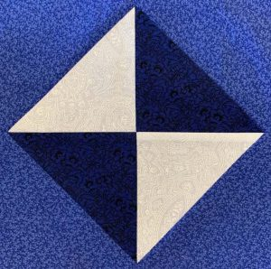 Blue, dark blue and white envelope-shaped pattern quilt block.