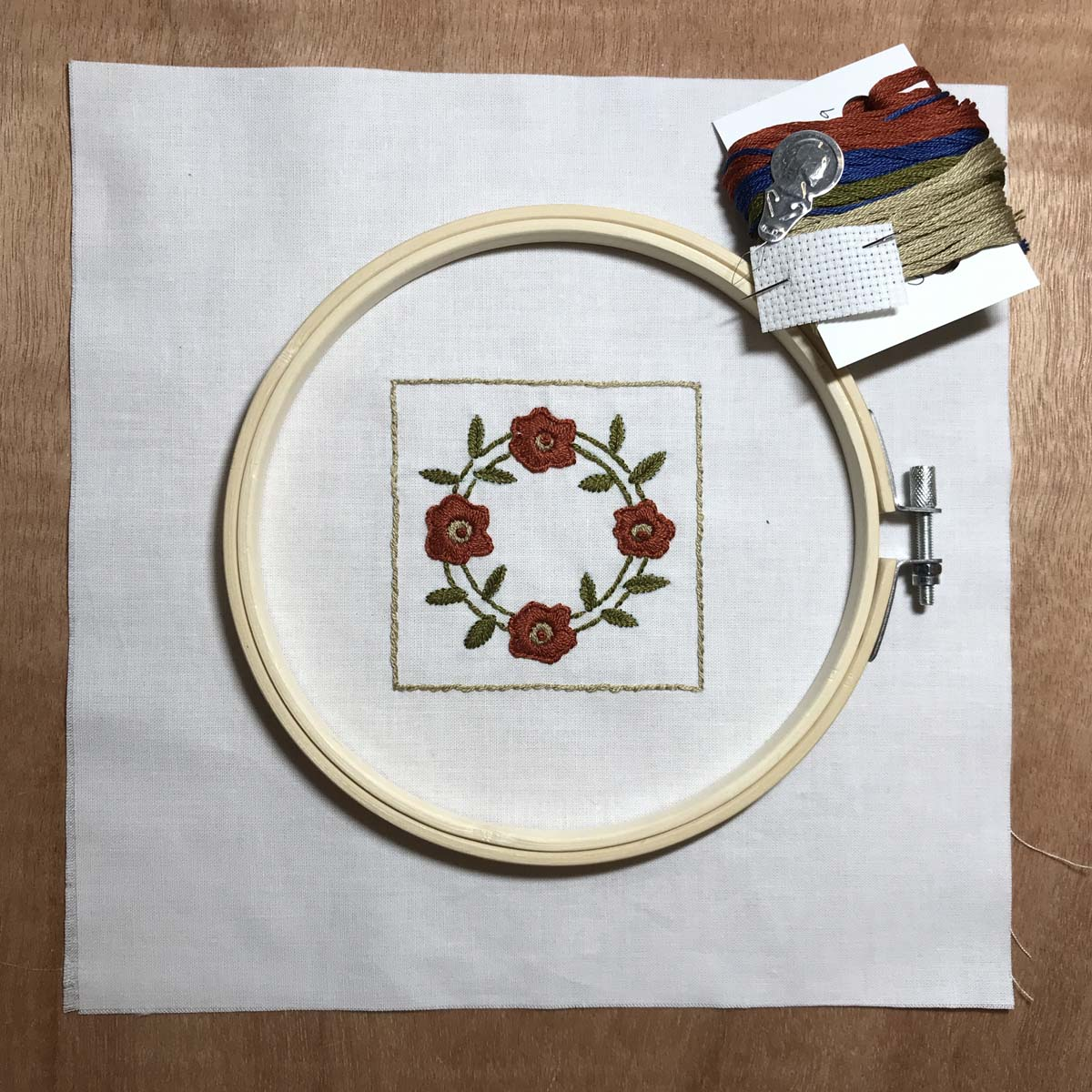 Miniature embroidered quilt block with hoop in the Rose Wreath pattern.