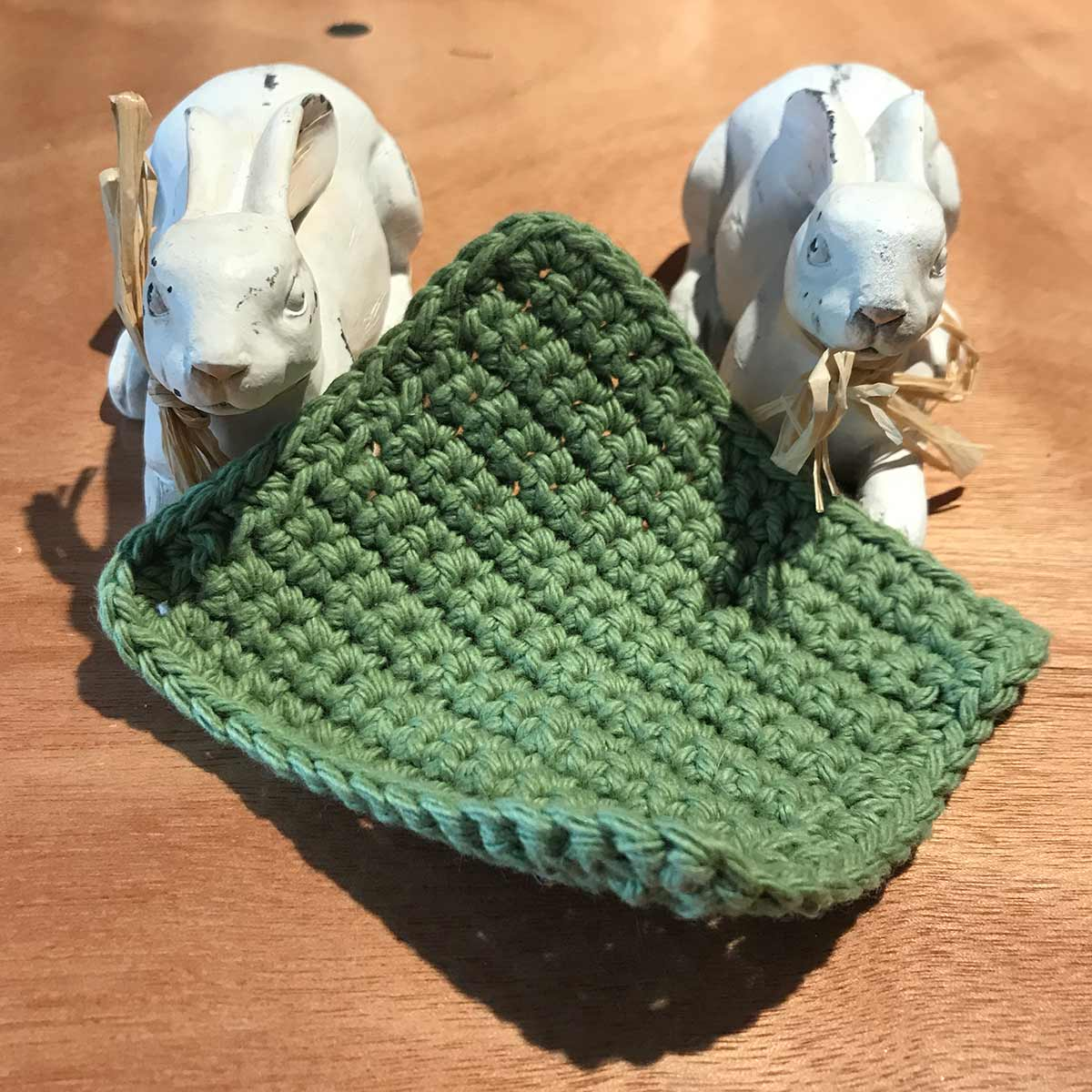 Olive green crochet coaster on table between two rabbits.