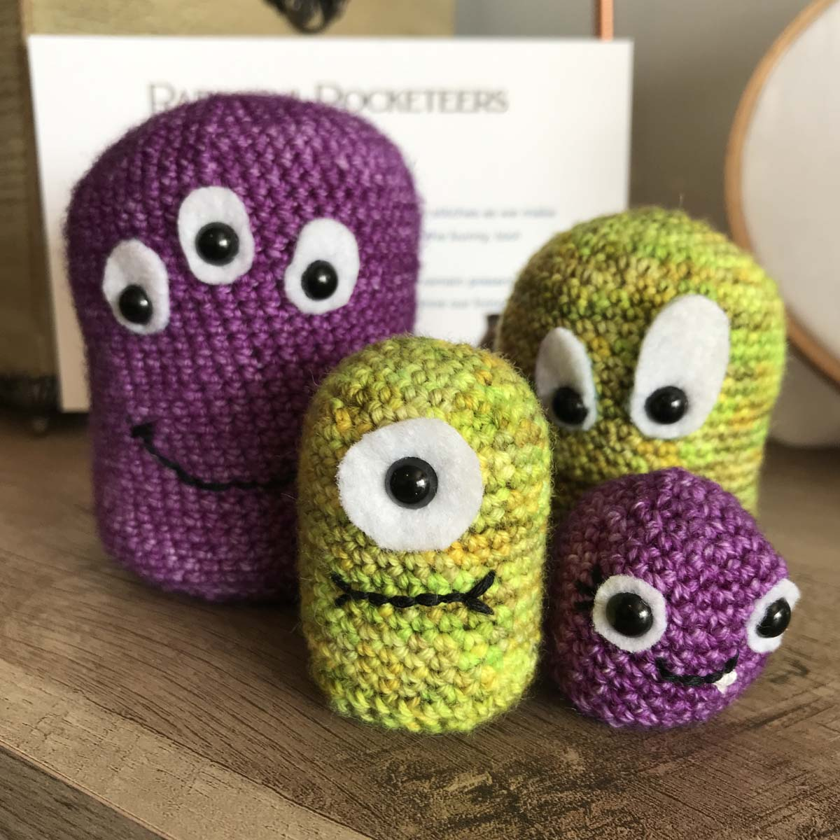 Selection of Amigurumi crocheted monsters in lime green and purple.