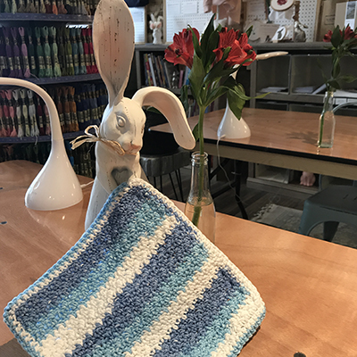 Carved rabbit on table with blue and white striped crochet dishcloth.