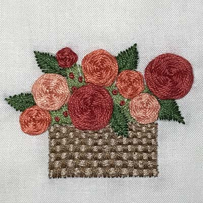 Embroidered basket on linen.