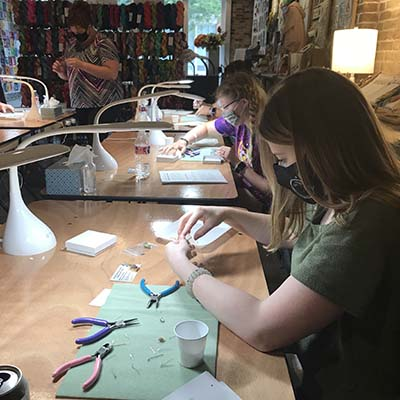 Women creating earrings in a jewelry class.